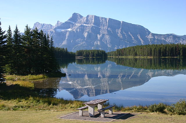 Scenic view of a picnic table beside a lake, forest, and mountains.