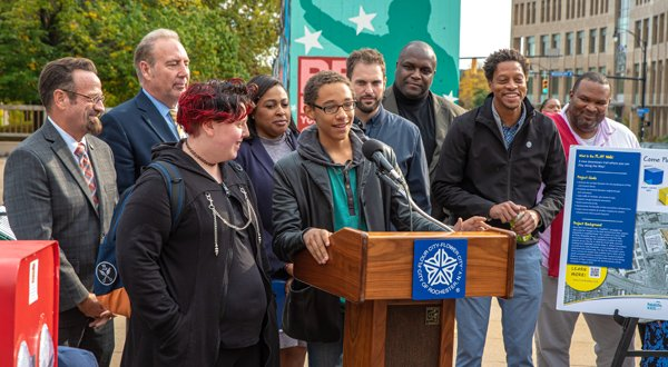People gather around a podium and a young person speaks into a microphone during the Play Walk grand opening Oct. 24.