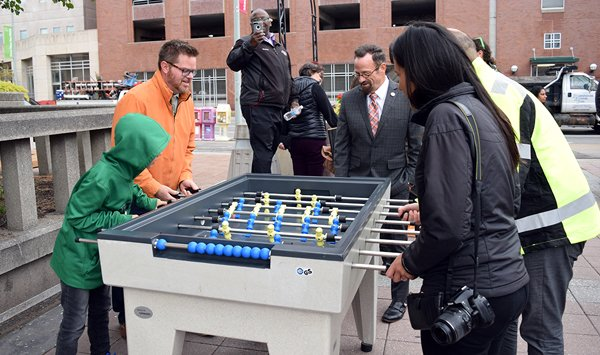 Four people play a yellow and blue table soccer game that is permanently installed outdoors on Rochester's Play Walk.