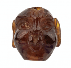 An Antique Japanese Amber Ojime Bead Of A Head