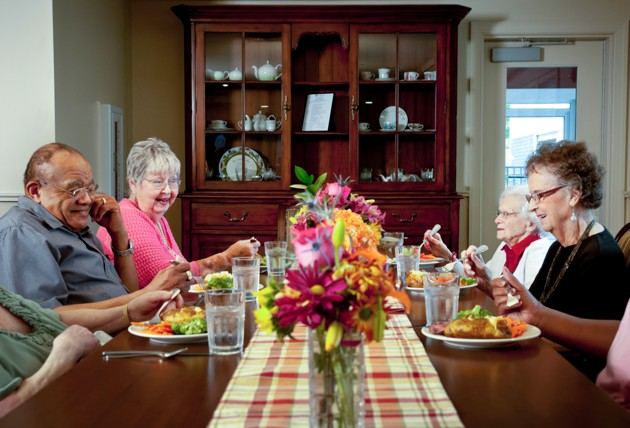 Elderly people having dinner at a table